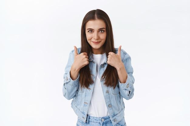 Animada, alegre, elegante, morena feminina caucasiana, em jaqueta jeans, mostrando o polegar para cima e sorrindo encantada, aprovo a ideia incrível e aceno com a cabeça, como boa oferta, fundo branco