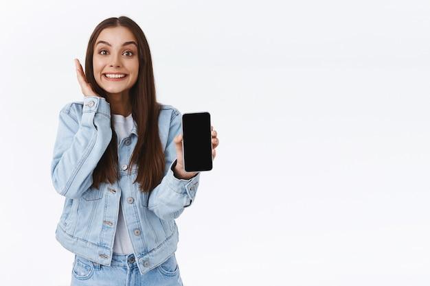 Animada, alegre, feliz, animada garota em jaqueta jeans, jeans, segurando um smartphone, mostrando a tela do celular reagindo a uma foto ou vídeo incrível online, tocando a bochecha e sorrindo maravilhada