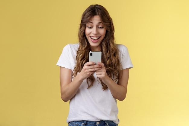 Animada, alegre, feliz, boba, de cabelos cacheados, receba notícias surpreendentes boas segurar smartphone sorrindo olhar encantado tela do celular respondendo convite de aniversário fundo amarelo otimista