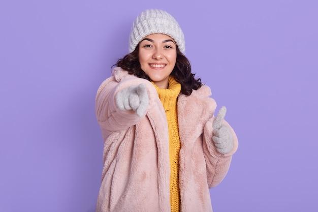 Animada, alegre, rindo, linda mulher bonita de cabeça escura, vestindo um casaco de pele quente e boné, encostada na parede lilás, apontando para a câmera com o dedo indicador
