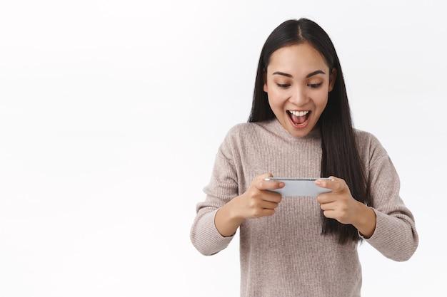 Animada, atônita, brincalhona jovem asiática do milênio assistindo a um vídeo divertido, jogando um jogo incrível, segurando o smartphone horizontalmente vencendo, torcendo e comemorando a vitória, conquiste o prêmio