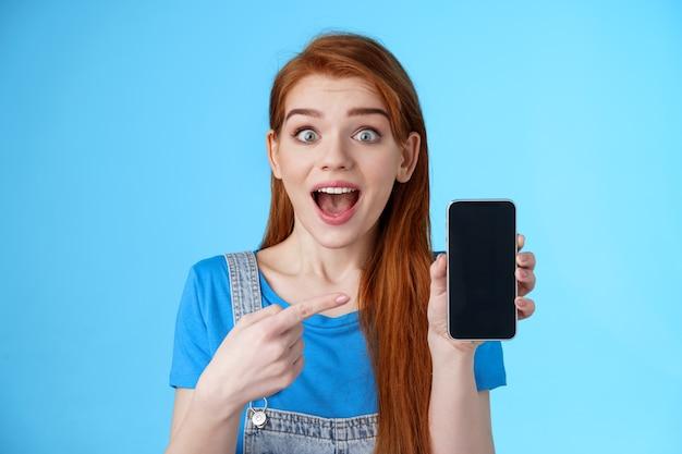 Animada, divertida, bonita, menina ruiva, promove aplicativo incrível, mostra a tela do smartphone, aponta a tela do telefone atônita, sorri surpresa, gosta de um jogo legal, fica com um fundo azul