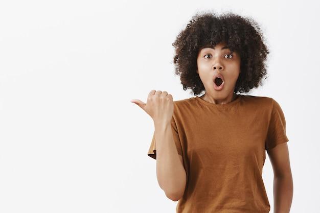 Animada e animada linda garota de pele escura com cabelo encaracolado em uma camiseta marrom da moda apontando para a esquerda com o polegar arfando e dizendo uau com a boca aberta dobrada sendo impressionada fazendo perguntas