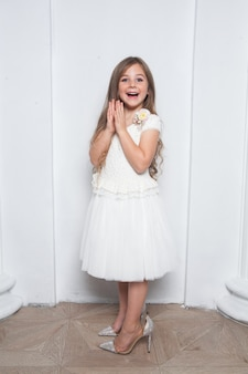 Animada e emocional linda garota com vestido branco da moda se divertindo e usando mães grandes e saltos altos brilhantes