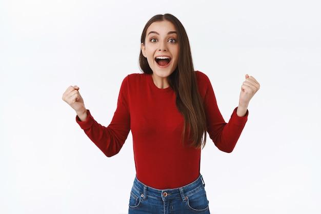 Animada e inspirada, menina morena animada em um suéter vermelho, punhos cerrados em triunfo, tendo aspirações sorrindo maravilhadas e maravilhadas, ver a vitória do time, alcançar objetivo ou sucesso, fundo branco