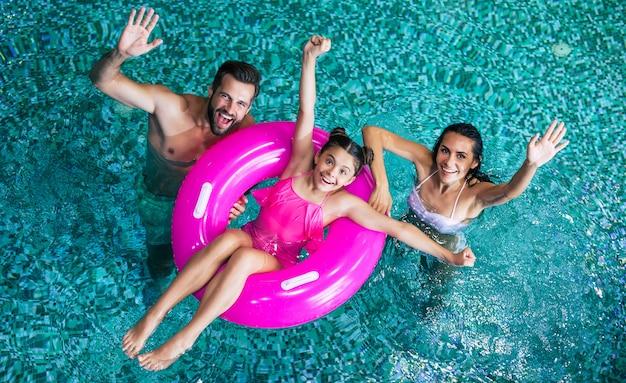 Animada e jovem família feliz em férias no hotel spa relaxe e se divirta na piscina. descanso de verão