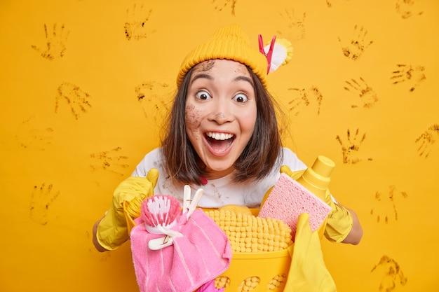 Animada e surpresa, a empregada asiática fica de boca aberta dizendo uau posa com cesto de roupa suja e agente de limpeza usa luvas protetoras de borracha isoladas sobre a parede amarela