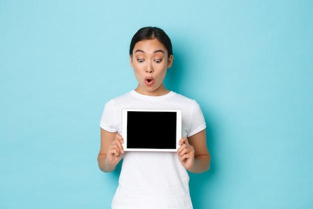 Animada e surpresa, linda mulher asiática em camiseta branca olhando para a tela do tablet digital com olhar surpreso e emocionado, mostrando gráfico ou demonstração de site de compra online, parede azul claro