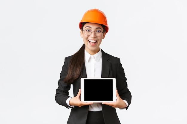 Animada e surpresa, sorridente, engenheira civil asiática, arquiteta com capacete de segurança e terno de negócios, mostrando a tela do tablet digital com expressão de espanto, fundo branco de pé