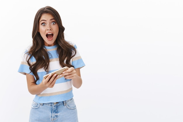 Animada, emotiva, alegre, linda garota, aprenda a jogar jogos para celular, segure smartphone horizontal, gritando