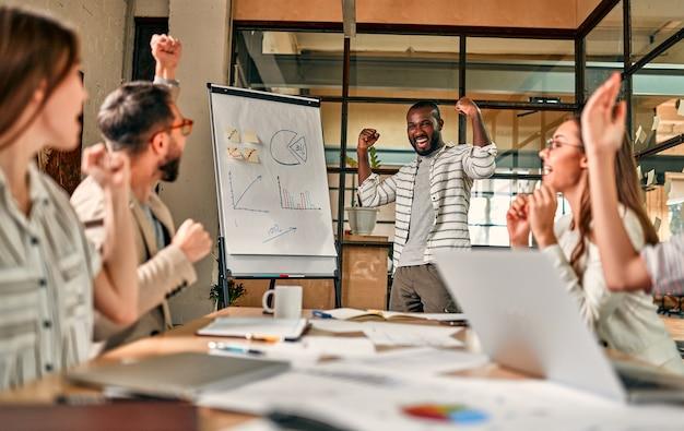 Animada equipe de negócios africana e caucasiana, motivada pela vitória, conquista ou bom desempenho, o grupo multinacional de funcionários comemoram juntos o sucesso corporativo.