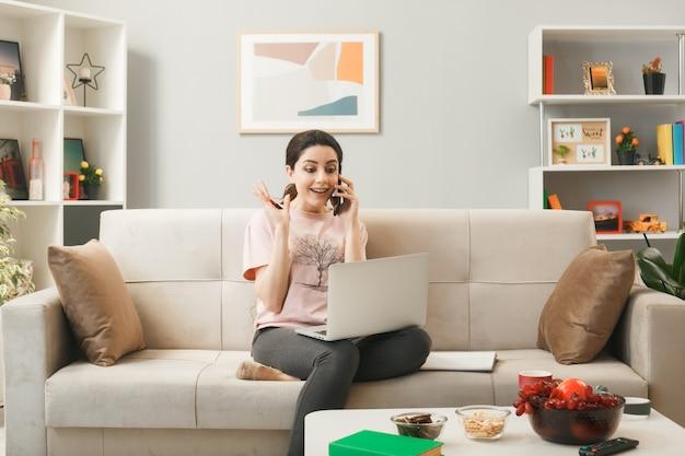 Animada, espalhando a mão jovem com laptop falando no telefone, sentada no sofá atrás da mesa de centro na sala de estar