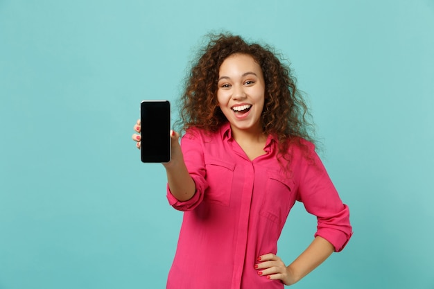 Animada garota africana com roupas casuais segura o telefone móvel com a tela em branco vazia, isolada no fundo da parede azul turquesa no estúdio. emoções sinceras de pessoas, conceito de estilo de vida. simule o espaço da cópia.