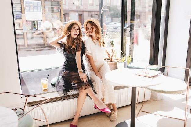 Animada garota de cabelos compridos em um vestido preto e sapatos roxos se divertindo em um café com uma linda amiga loira