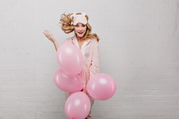 Animada garota loira de pijama rosa segurando um monte de balões de hélio. retrato interior de uma jovem inspirada na máscara de dormir da moda dançando na parede de luz.