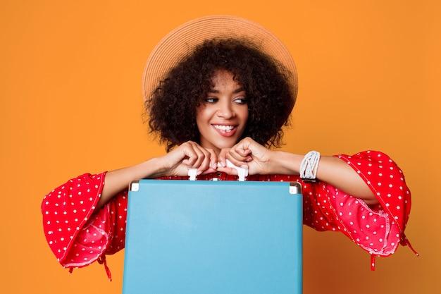 Animada garota negra com penteado africano segurando uma linda mala azul.