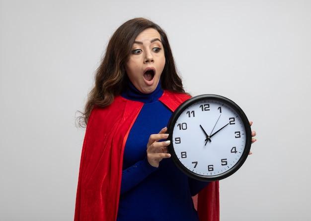 Animada garota super-heroína caucasiana com capa vermelha segura e olha para o relógio isolado na parede branca com espaço de cópia