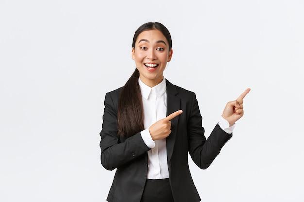 Animada gerente, vendedora ou corretora imobiliária asiática mostrando a casa à venda, apontando o dedo para a direita, comerciante apresenta o projeto ou gráfico na reunião de negócios, em pé no fundo branco do terno