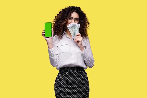 Animada jovem americana segurar o telefone móvel com o ventilador de tela vazia em branco de dinheiro em notas de dólar. posando isolado na parede amarela.