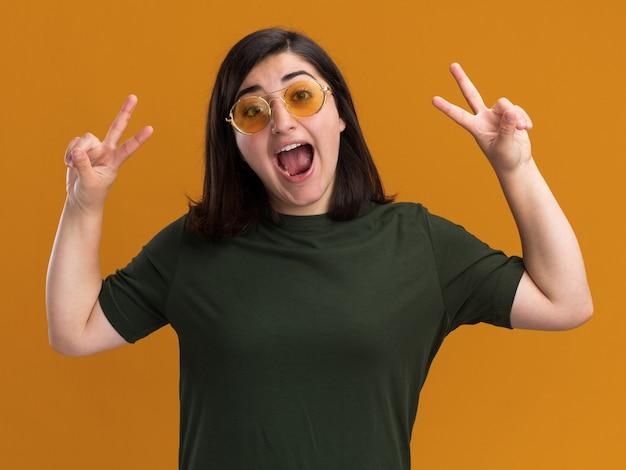 Animada, jovem, bonita, caucasiana, usando óculos de sol, gesticulando o sinal da vitória com as duas mãos, isolada na parede laranja com espaço de cópia