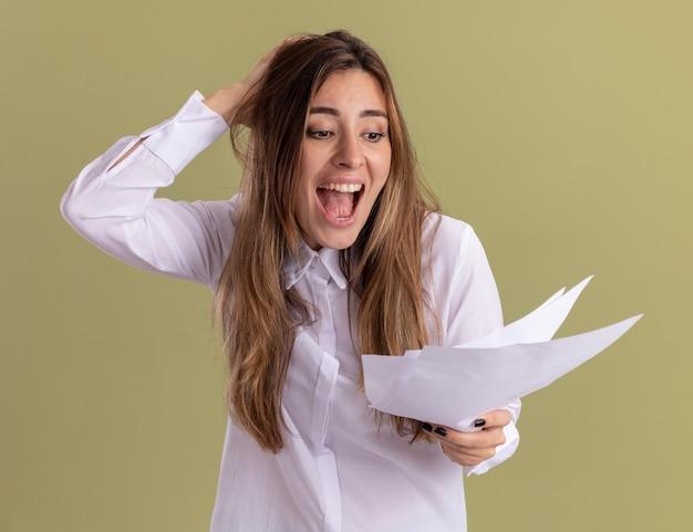 Animada, jovem e bonita caucasiana coloca a mão na cabeça, segurando e olhando para as folhas de papel em branco no verde oliva