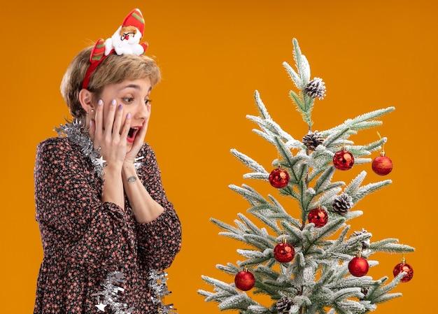 Animada, jovem e bonita garota usando bandana de papai noel e guirlanda de ouropel em volta do pescoço em pé perto da árvore de natal decorada, mantendo as mãos no rosto olhando para baixo, isolado em um fundo laranja