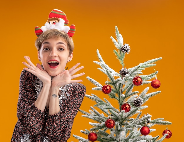 Animada, jovem e bonita garota usando uma faixa de papai noel e guirlanda de ouropel no pescoço, em pé perto da árvore de natal decorada, olhando para a câmera, mantendo as mãos sob a cabeça isoladas em fundo laranja