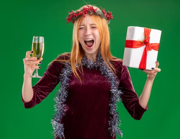 Animada jovem linda com vestido vermelho com coroa de flores e guirlanda no pescoço segurando uma taça de champanhe com caixa de presente isolada no fundo verde