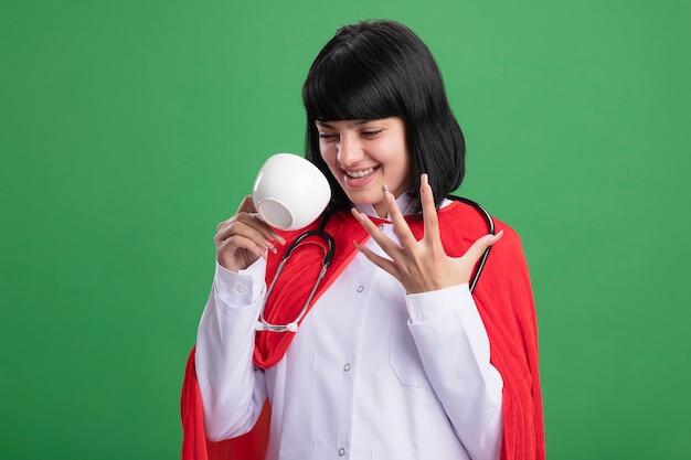 Animada jovem super-heroína usando estetoscópio com manto médico e capa segurando e olhando para o copo isolado no verde