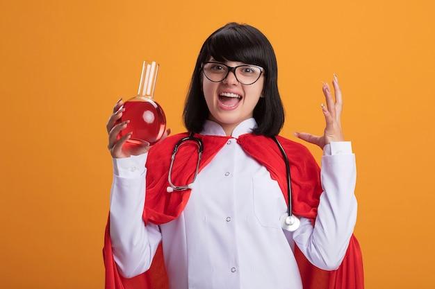 Animada jovem super-heroína usando estetoscópio com túnica médica e capa com óculos segurando uma garrafa de vidro de química cheia de líquido vermelho espalhando a mão