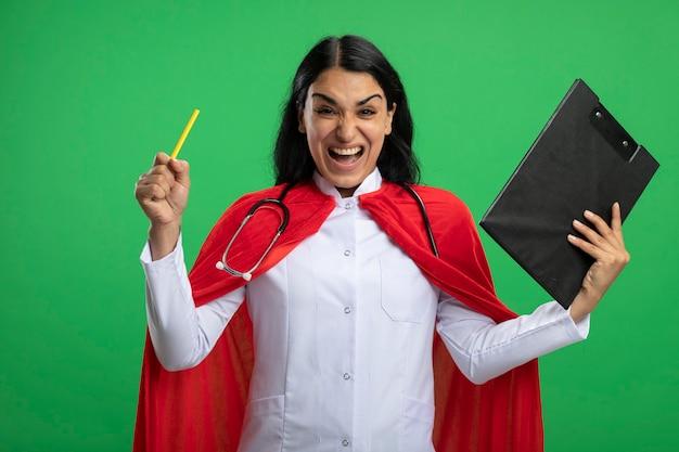 Animada jovem super-heroína vestindo túnica médica com estetoscópio segurando uma prancheta com lápis isolado no verde