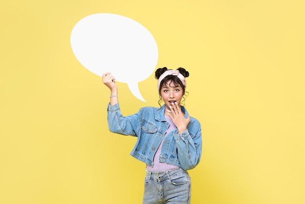 Animada menina adolescente asiática segurando balões de fala em branco sobre fundo amarelo.