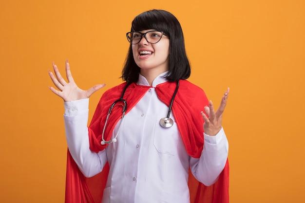 Animada, olhando para o lado, a jovem super-heroína usando estetoscópio com túnica médica e capa com óculos estendendo as mãos