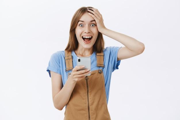 Animada regozijando-se com a linda garota reagindo a notícias incríveis online, segurando um smartphone e parecendo fascinada