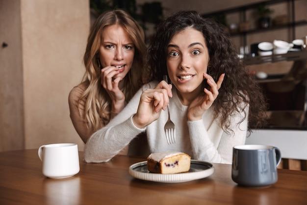 Animadas, confusas, famintas, lindas amigas sentadas em um café tomando café e comendo bolo