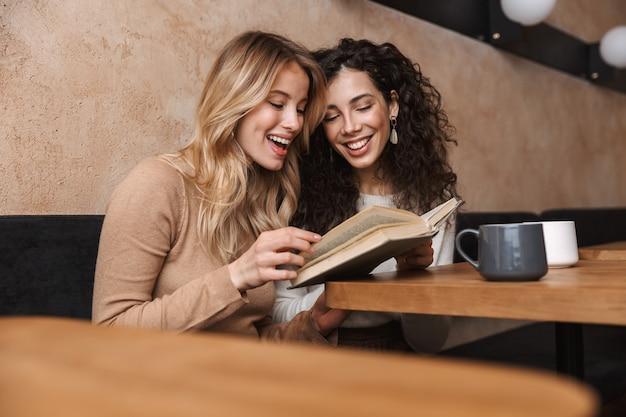 Animadas e felizes amigas bonitas sentadas em um café, bebendo café, lendo um livro