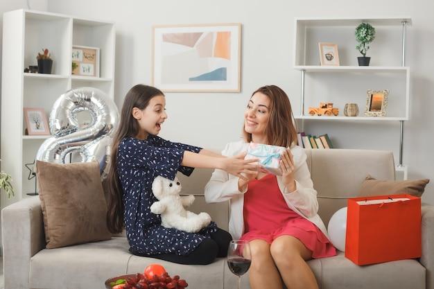 Animadas olhando uma para a outra, garotinha e mãe com presente e ursinho de pelúcia no dia da mulher feliz, sentada no sofá da sala