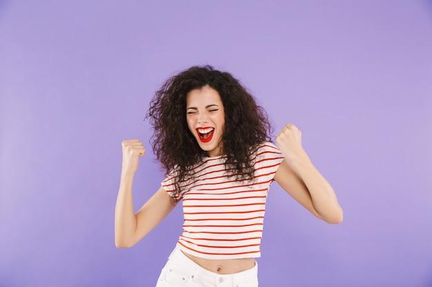 Animado alegre mulher com cabelos cacheados no verão usar gritando e cerrando os punhos