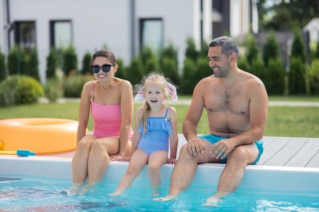 Animado antes de nadar. filha loira alegre e animada antes de nadar na piscina com os pais