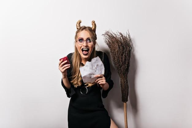 Animado assistente feminino rindo no halloween. feliz jovem bruxa de óculos, expressando felicidade.