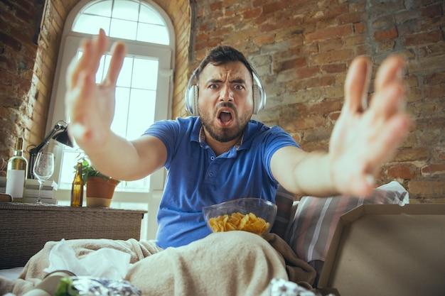 Animado assistindo jogo do time favorito. homem preguiçoso que vive em sua cama rodeado de bagunça. não precisa sair para ser feliz. usar gadgets, assistir filmes e séries, parece emocional. comida rápida.