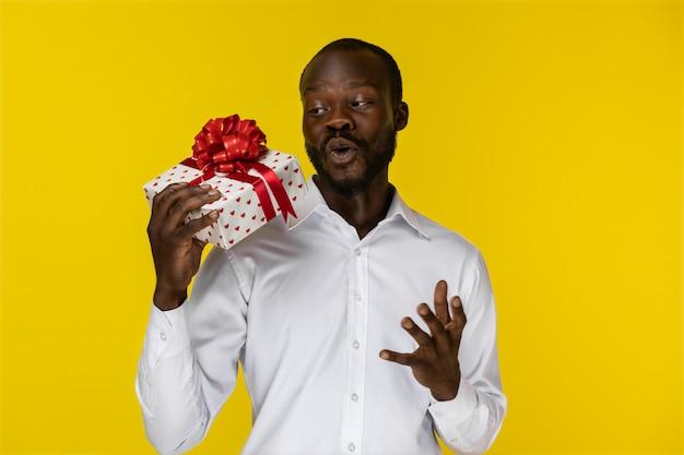 Animado barbudo jovem afro-americano está segurando um presente em uma mão
