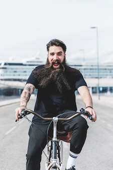 Animado barbudo jovem desfrutando de andar de bicicleta