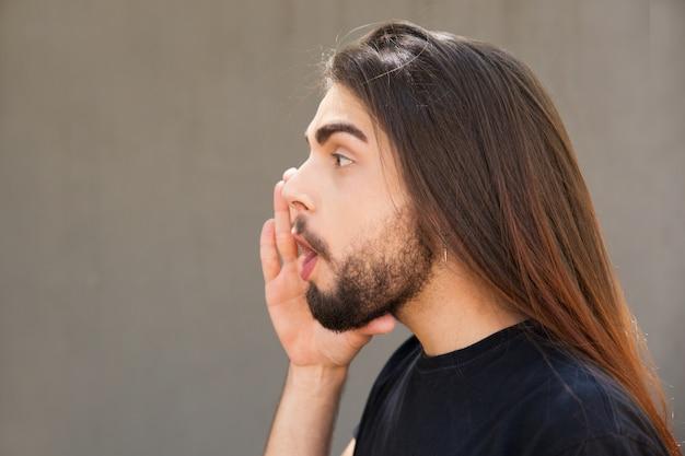Animado cara de cabelos compridos, anunciando notícias importantes