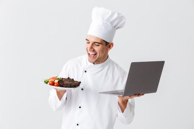 Animado chef cozinheiro usando uniforme em pé sobre uma parede branca, segurando um laptop, mostrando um prato