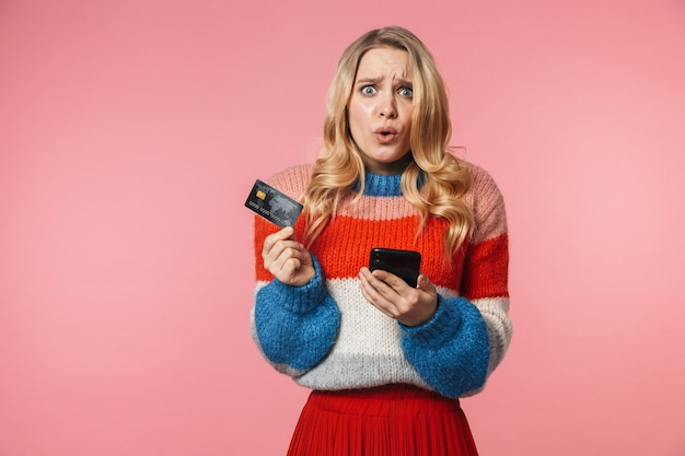 Animado chocado jovem linda mulher posando isolada sobre uma parede rosa usando um telefone celular segurando um cartão de crédito