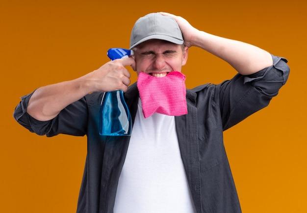Animado com os olhos fechados, jovem cara de limpeza bonito vestindo camiseta e boné, segurando um pano na boca, colocando o spray no templo isolado na parede laranja