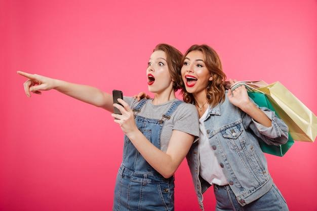 Animado duas mulheres amigos segurando sacolas usando telefone celular.