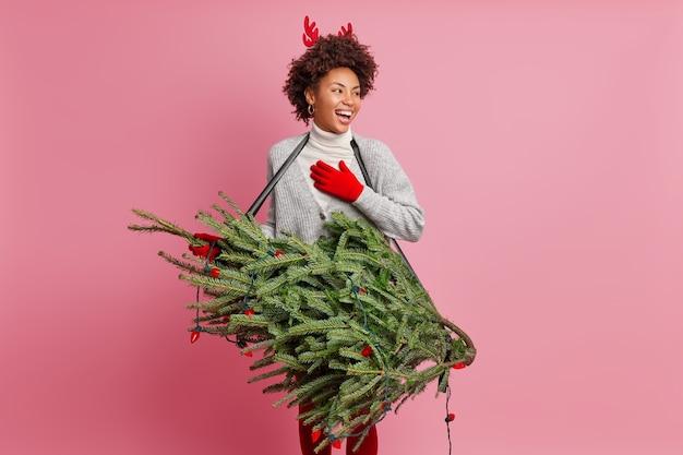 Animado e alegre guitarrista feminino segura árvore de abeto finge tocar guitarra brincalhões na véspera de ano novo usa luvas vermelhas, chifres de rena desvia o olhar e se prepara para o evento festivo. época de natal
