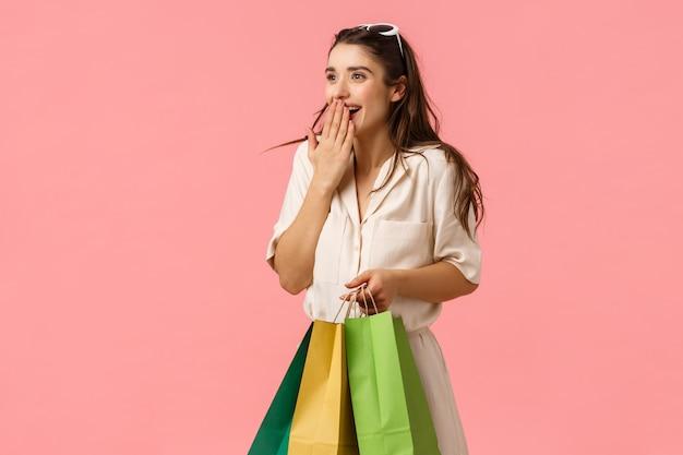 Animado e fascinado feminino morena feminina bonito vestido, segurando sacolas de compras, maravilha ao redor do shopping, ofegante boca de capa animada vendo algo maravilhoso, rosa